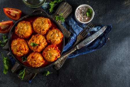 Homemade chicken meatballs in tomato sauce in a frying pan on dark stone or concrete table. Top view copy space Фото со стока