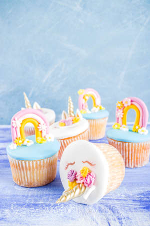 Cute unicorn and rainbow cupcakes, light blue background, copy space