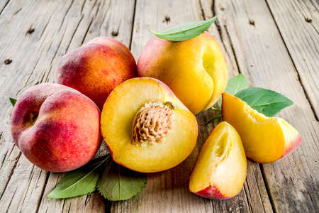 Fresh organic peaches, whole and sliced, with leaves, on rustic wooden background Stock fotó
