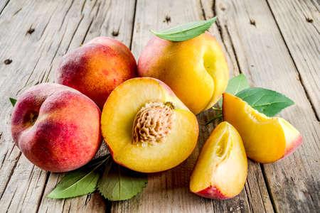 Frische Bio-Pfirsiche, ganz und in Scheiben, mit Blättern, auf rustikalem Holzhintergrund