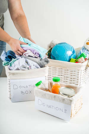 Giving and helping concept. Reuse and recycling theme. Donation box with clothes, childrens toys, food. On a white background