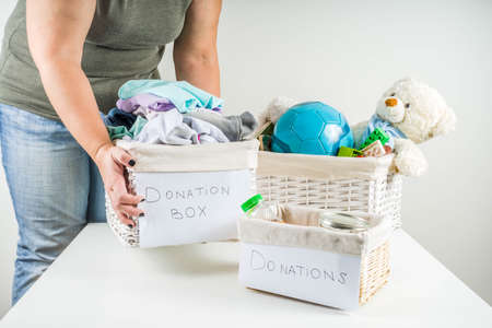 Giving and helping concept. Reuse and recycling theme. Woman holds and folds donation box with clothes, childrens toys, food. On a white background, Girls hands in picture Stock fotó