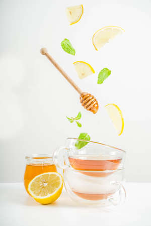 Autumn tea with mint and lemon with ingredients - fresh mint leaves, sliced lemon and honey, white background copy space