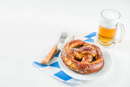 Oktoberfest festive cutlery set  with with a traditional checkered  tablecloth, plate, pretzel, fork, knife and a glass of beer. background for Restoration menu Stok Fotoğraf