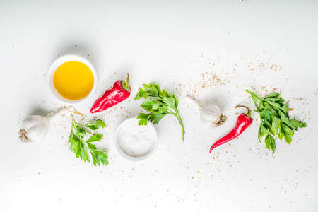 Herb and spices cooking background. Olive oil, salt, garlic, parsley, hot red peppers chili, for cooking  homemade dinner. On a white background, copy space top view Stock Photo - 129757915