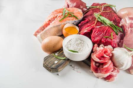 Carnivore diet background. Non vegan protein sources, Different meat food - chicken breast, pork steak, beef tenderloin, eggs, spices for cooking. White marble background copy space Foto de archivo - 129903509