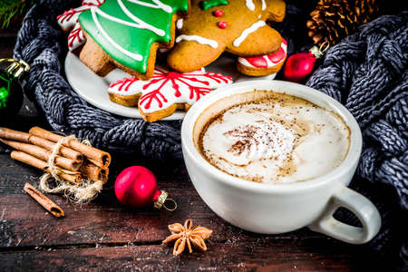 Traditional christmas sweet treats, colorful sugar glazed homemade gingerbread cookies with xmas tree, decoration, spices and coffee latte mud on classic wooden background