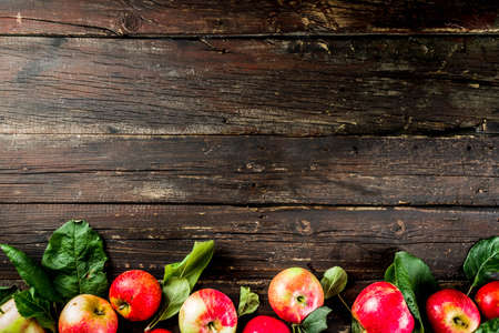 Autumn organic homemade apples, with leaves, on a wooden rustic table Banco de Imagens