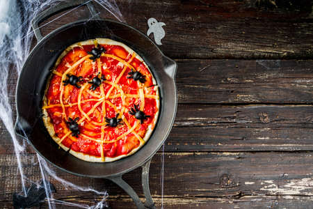 Halloween Spiderweb Pizza. Homemade kids party dish with tomato sauce, cheese and olive spiders. Funny and easy food ideas for kids Halloween party. Old rustic wooden background