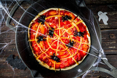 Halloween Spiderweb Pizza. Homemade kids party dish with tomato sauce, cheese and olive spiders. Funny and easy food ideas for kids Halloween party. Old rustic wooden background top view