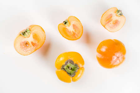 Whole and sliced persimmons, fresh organic farm fruit on a white background. Isolated, copy space Stock Photo