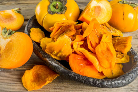 Dried persimmon fruit, with fresh persimmons, on wooden rustic background copy space 스톡 콘텐츠