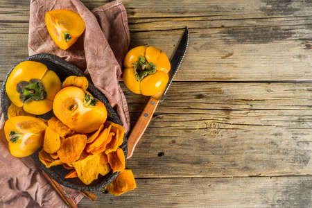 Dried persimmon fruit, with fresh persimmons, on wooden rustic background copy space Stock Photo