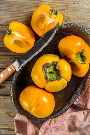 Whole and sliced persimmons, fresh organic farm fruit on rustic wooden background. Isolated, copy space Stock Photo