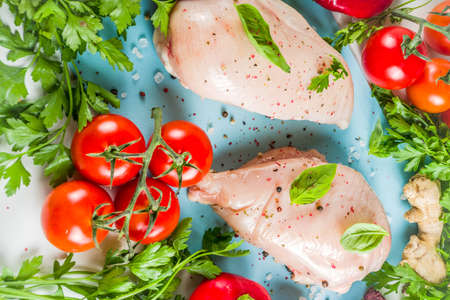 Raw chicken fillet with spices and herbs on cutting board. Cooking chicken background. Preparation food, Diet healthy meat.