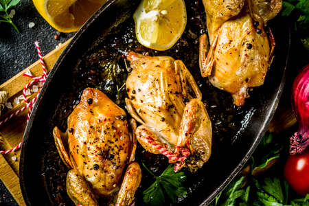 Delicious fried roasted quails with herbs, spices and greens. Grilled quails carcasses in a baking dish. Holiday Christmas and Thanksgiving meal concept. Stock fotó