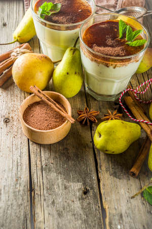 Autumn healthy drinks and snacks. Pear smoothie with cocoa chocolate and spices - cinnamon, anise, with mint leaves. On a rustic wooden background, copy space