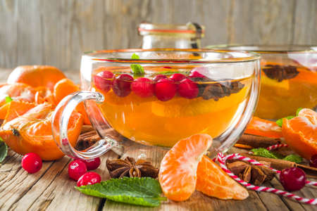 Autumn winter spicy hot citrus tea with tangerines, cranberries, honey and spices. On a wooden background, copy space