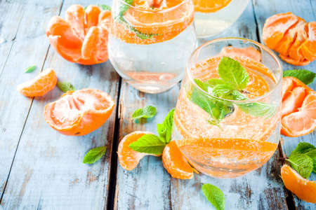 Summer tangerine citrus drink, lemonade or mojito, with fresh tangerines, lemons and mint on a blue wooden table,