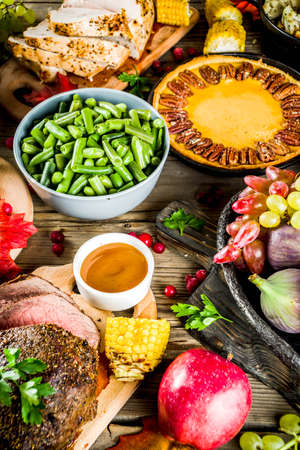 Thanksgiving family dinner setting concept. Traditional Thanksgiving day food  with turkey, green beans and mashed potatoes, stuffing, pumpkin, apple and pecan pies, rustic wooden table Imagens