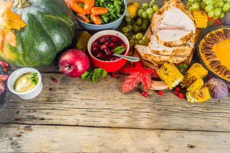 Thanksgiving family dinner setting concept. Traditional Thanksgiving day food  with turkey, green beans and mashed potatoes, stuffing, pumpkin, apple and pecan pies, rustic wooden table 写真素材 - 130405575
