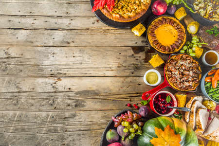 Thanksgiving family dinner setting concept. Traditional Thanksgiving day food  with turkey, green beans and mashed potatoes, stuffing, pumpkin, apple and pecan pies, rustic wooden table Фото со стока