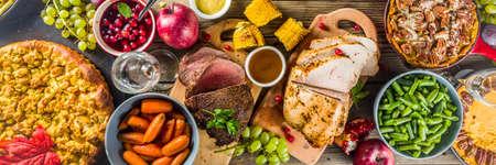 Thanksgiving-Familienessen Einstellung Konzept. Traditionelles Thanksgiving-Essen mit Truthahn, grünen Bohnen und Kartoffelpüree, Füllung, Kürbis-, Apfel- und Pekannusstorten, rustikales Holztischbanner Standard-Bild
