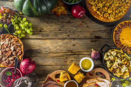 Thanksgiving family dinner setting concept. Traditional Thanksgiving day food  with turkey, green beans and mashed potatoes, stuffing, pumpkin, apple and pecan pies, rustic wooden table frame