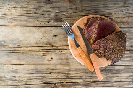 Baked tenderloin beef meat on a cutting board on a wooden background copy space