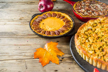 Traditional seasonal autumn pies - pumpkin, pecan and apple crumble cakes, wooden background Imagens