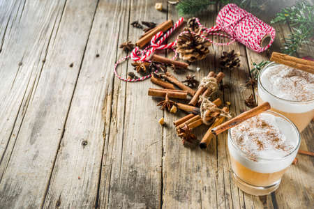Autumn winter hot toddy alcohol cocktail with spices, wooden background with christmas decorations. Christmas beverage idea recipe, copy space