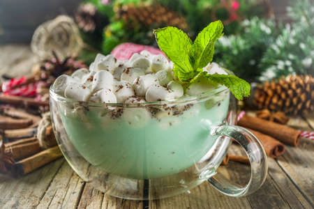 Homemade peppermint green colored mint white hot chocolate, with christmas decorations on wooden table. Christmas hot cocoa drink recipe.