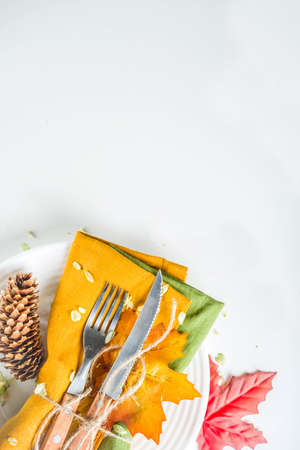Autumn cutlery background. Fall card background for menu or invitation, banner format. With fork, knife, napkins, pumpkin, plate, multicolored leaves. On white table, top view copy space Imagens