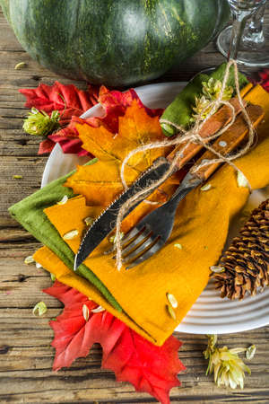 Autumn cutlery background. Fall card background for menu or invitation, banner format. With fork, knife, napkins, pumpkin, plate, multicolored leaves. On rustic old wooden table, top view copy space