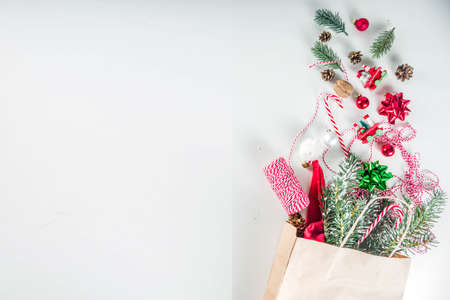 Christmas preparation concept. Paper bag with xmas and New Year decorations - Christmas tree branches, balls, holiday ribbon, cones. On a white background flat lay copy space