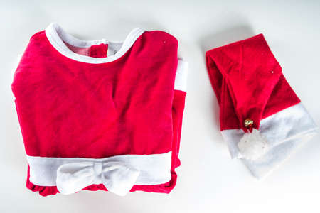Christmas preparation concept. Christmas dress Santa Claus for girl, with santas hat and New Years gifts. On a white background, top view flat lay copy space Imagens