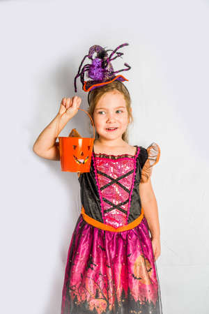 Little cute girl in witch costume for Halloween with jack-o-lantern bucket for Halloween trick or treating. White wall background copy space