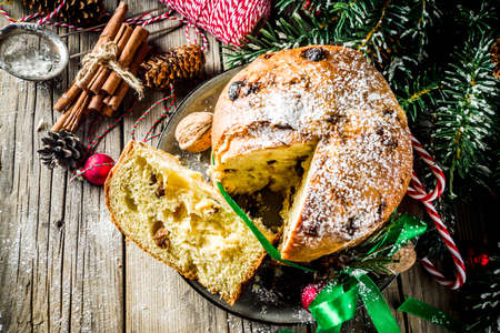 Traditional Christmas panettone with dried fruits and nuts, on old wooden background with christmas decoration copy space top view 写真素材