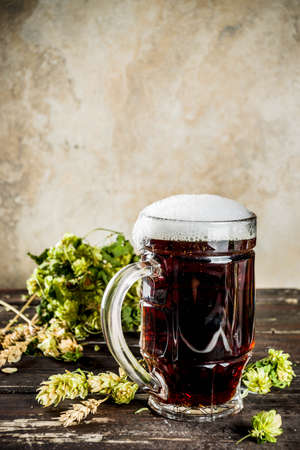 Dark beer ale mug on a wooden background with hops and wheat