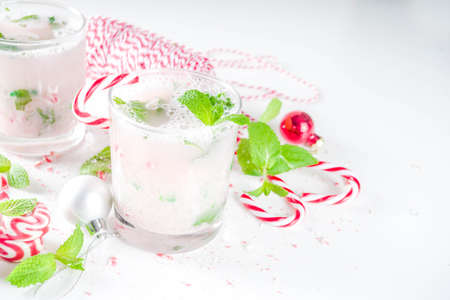 Christmas candy cane mojito cocktails with sweet. fresh mint and christmas decoration on white table