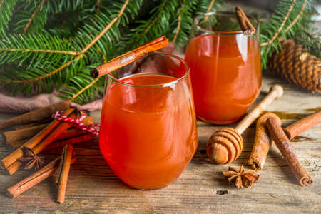 Winter and Christmas alcohol drink, Wassail hot cocktail with spices, wooden background copy space