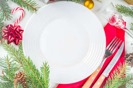Christmas festive table setting with with a plate, fork, Christmas decorations, gift boxes, fir tree branches, glass and champagne bottle. Holiday table background copy space 스톡 콘텐츠