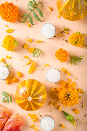 Traditional autumn mexican holiday, with Marigold flowers, candles, autumn leaves and pumpkins.