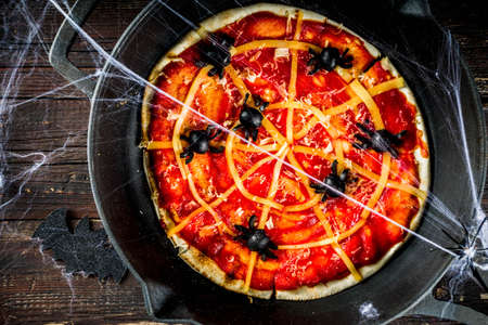 Halloween Spiderweb Pizza. Homemade kids party dish with tomato sauce, cheese and olive spiders.