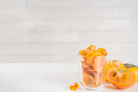 Dried persimmon fruit, with fresh persimmons, on white concrete or stone