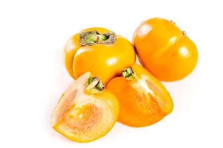 Whole and sliced persimmons, fresh organic farm fruit on a white