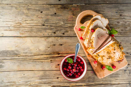 Baked turkey breast fillet with cranberry sauce, on a cutting board wooden rustic