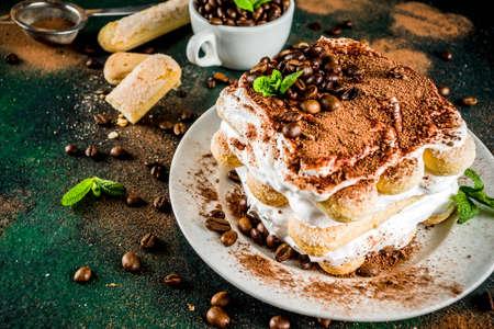 Homemade Italian dessert tiramisu on plate, with cocoa and coffee beans
