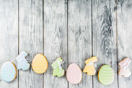 Easter greeting card  with pastel colored eggs and homemade cookies shaped in eggs and bunnies rabbits.