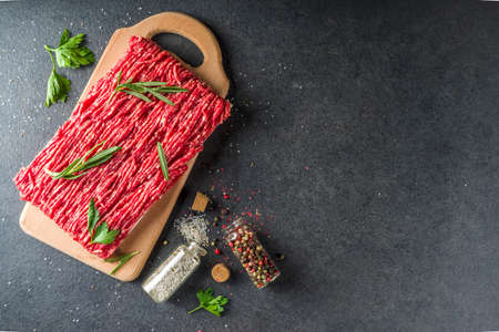 Raw minced beef meat with herbs and spices for cooking, black concrete or stone table 스톡 콘텐츠
